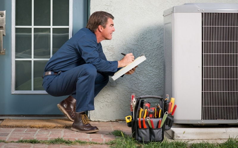 An HVAC technician in Santa Rosa, CA, performing a spring maintenance inspection on an air conditioner.