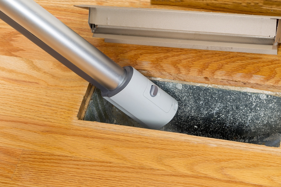 This is a horizontal photo of vacuum cleaning inside heater floor vent with Red Oak Floors in background.