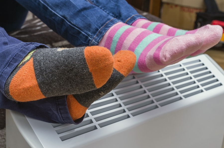 Homeowners with their feet over furnace staying warm after scheduling their fall furnace clean and check.
