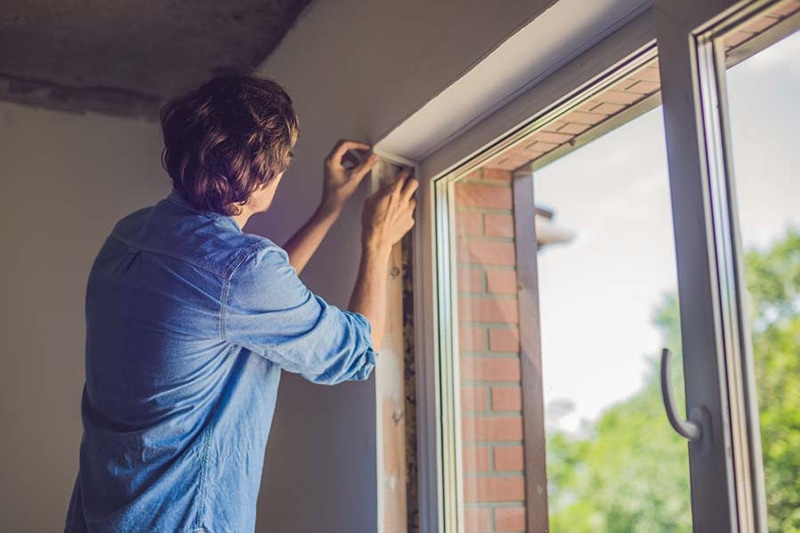 Man checking window sealing after following the tips he received on heat gain prevention in his home.