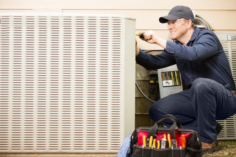 Technician working on a air conditioning unit showing why you should join the HVAC industry.